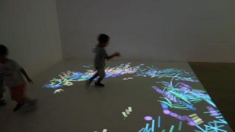 光の積み木を追いかける子ども