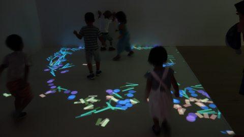 光の積み木を蹴散らして遊ぶ子ども